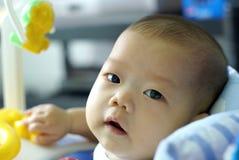 Het babymeisje zit op autostuk speelgoed en het zoeken van iets royalty-vrije stock foto
