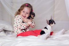 Het babymeisje zit op bed en koestert kleine hond Royalty-vrije Stock Fotografie