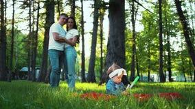 Het babymeisje zit op deken op groen gras en de ouders bekijken haar van afstand stock footage