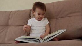 Het babymeisje zit op zachte laag het glimlachen draaien de pagina's van een kleurrijk boek stock video