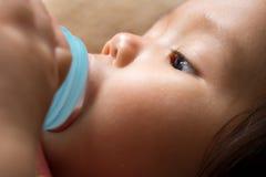 Het babymeisje zuigt melk van fles vóór slaap Stock Foto