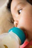 Het babymeisje zuigt melk van fles vóór slaap Stock Afbeelding