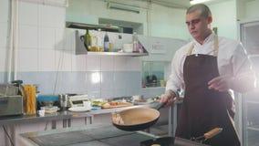 Het bacon van chef-kokgebraden gerechten in een pan in het restaurant stock footage