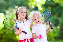 Het badminton of het tennis van het jonge geitjesspel in openluchthof Stock Foto