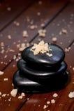 Het badzout van het kuuroord op een stapel saldo zen stenen Stock Fotografie