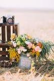 Het bakhoogtepunt van kleurrijke bloemen wordt geplaatst dichtbij de donkere houten dozen met de camera bij de achtergrond van zo Stock Foto