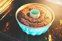 Het bakken van de bundtcake in de oven Stock Foto's