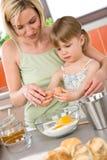 Het bakken - Vrouw met kind dat deeg voorbereidt stock foto's