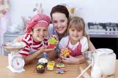 Het baksel van de moeder met kinderen in de keuken Stock Afbeeldingen
