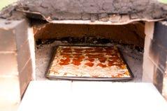 Het baksel van de pizza in aarden oven Royalty-vrije Stock Fotografie