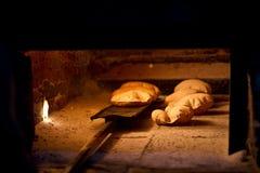 Het baksel van het brood in een open traditionele brandhoutoven stock foto's
