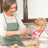 Het bakselkoekjes van de grootmoeder en van de kleindochter royalty-vrije stock afbeelding