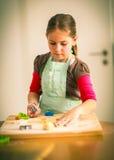 Het bakselkoekjes van het schoolmeisje Stock Foto's