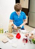 Het bakselmuffins van het jongensjonge geitje Kind die schooler muffins in de keuken voorbereiden stock afbeelding