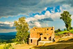 Het baksteenhuis bouwde de bergen in stock fotografie