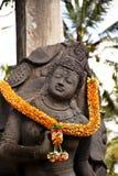 Het Balinese hinduistic standbeeld van het steenbeeldhouwwerk met het gele aanbieden stock afbeeldingen