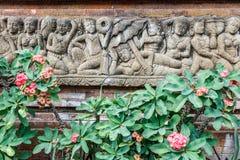 Het Balinese steen snijden op de miliiinstallatie van de muur dichtbij bloeiende Wolfsmelk Bali, Indonesië stock fotografie