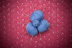 Is het ballen blauwe garen op het roze breigoed Stock Foto