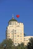 Het ballonhart over een high-rise gebouw Stock Foto