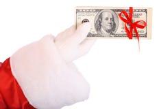 Het bankbiljet van de dollar in de hand van de Kerstman. Stock Foto