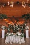 Het banket van de huwelijkslijst verfraaide met bloemen en installaties, retro lampen op een houten achtergrond royalty-vrije stock afbeeldingen