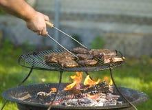 Mensen barbecuing vlees Royalty-vrije Stock Afbeeldingen