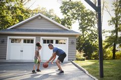 Het Basketbal van vaderand son playing op Oprijlaan thuis royalty-vrije stock afbeelding