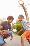 Het Basketbal van vaderwith son playing in Park samen Stock Foto