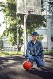 Het basketbalspeler van de tienerjongen met bal in openlucht royalty-vrije stock afbeeldingen