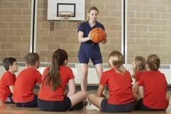 Het Basketbalteam van busGiving Team Talk To Elementary School Stock Afbeeldingen