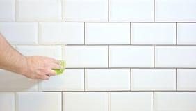 Het beëindigen van het betegelen van de keuken met witte tegels Stock Foto's