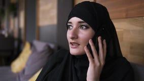 Het beantwoorden van het telefoongesprek Jonge vrij moslimvrouw met make-up in hijab die bij telefoon en glimlachen spreken, die  stock video