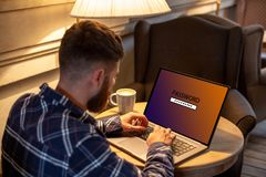 Het bebouwde beeld van een jonge mens die aan zijn laptop in een koffiewinkel werken, jonge mannelijke student gaat een wachtwoor royalty-vrije stock afbeeldingen