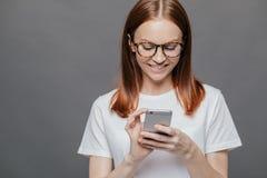 Het bebouwde beeld van mooie vrouw met vrolijke uitdrukking, glimlachen ruim, houdt mobiele telefoon, gelukkig om bericht van te  stock afbeeldingen