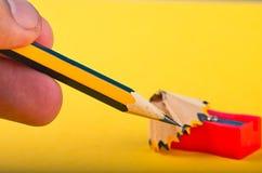 Het bebouwde grafiet houten potlood van de handholding op gele achtergrond stock foto's