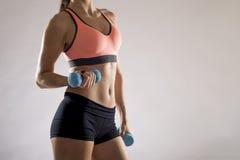 Het bebouwde lichaam dicht van jonge aantrekkelijke vrouw in sport kleedt omhoog het houden van gewichtsdomoor stock fotografie
