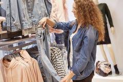 Het bebouwde schot van krullende vrouw in denimjasje, houdt jeans op hangers, kiest nieuwe aankoop voor zich, stelt in kledingsop royalty-vrije stock fotografie