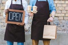 het bebouwde schot van twee multi-etnische eigenaars van de holding van de koffiewinkel ondertekent open, document zakken en besc royalty-vrije stock foto