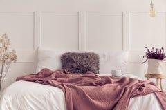 Het bed van de koningsgrootte met wit beddegoed en vuile roze algemene, echte foto met exemplaarruimte royalty-vrije stock afbeelding