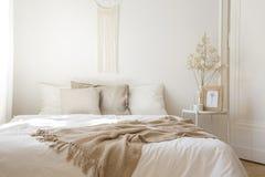 Het bed van de koningsgrootte met witte en beige hoofdkussens, echte foto royalty-vrije stock afbeeldingen