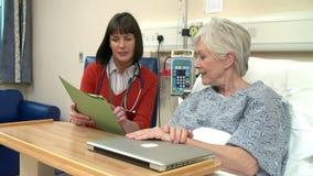Het Bed van de Patiënt van artsensitting by female in het Ziekenhuis stock footage