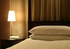 Het Bed van het hotel & de Lijst van de Nacht Stock Foto