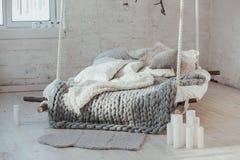 Het bed van het plafond wordt opgeschort dat De grijze grote comfortabele deken breit Skandinavische stijl, grijze plaid, kaarsen Stock Foto