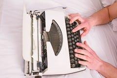 Het bed wit beddegoed die van de handenschrijver aan nieuw boek werken Schrijversauteur aan ouderwetse machine die in plaats van  stock fotografie