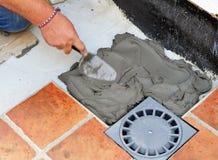 Het bedekken van de vloer van de binnenplaats van een huis met keramische tegel Royalty-vrije Stock Afbeelding