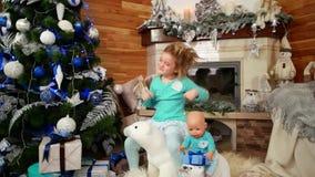 Het bedorven meisje lacht cheerfully, danst, stelt gezichten, Kind bij de zitting van het partijmeisje onder speelgoed in het lev stock footage