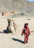 Het bedouin meisje die alleen in de woestijn tegen de achtergrond van een het liggen kameel en heuvels lopen Royalty-vrije Stock Afbeelding