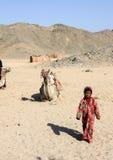 Het bedouin meisje die alleen in de woestijn tegen de achtergrond van een het liggen kameel en heuvels lopen Stock Foto