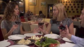 Het bedrijf die en drinkt wijn in restaurant babbelen stock footage