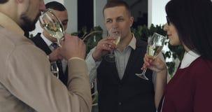 Het bedrijf houdt glazen met champagne en gerinkel stock videobeelden